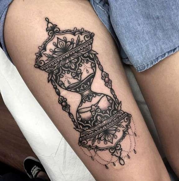 Tatuaje de reloj de arena en el muslo